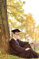 College graduate sitting by a tree in a park