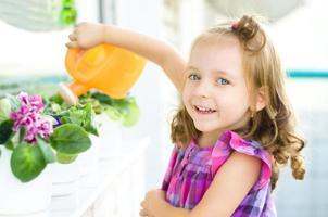 child watering flowers photo