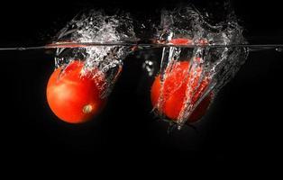 Fresh tomato dropped into water