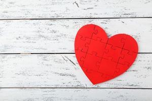 rode puzzel hart op witte houten achtergrond