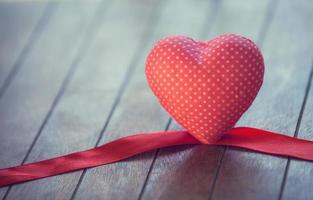 corazón y arco en la mesa de madera foto