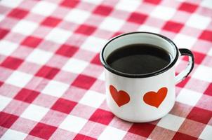Cup of coffee served in an old enamel mug photo