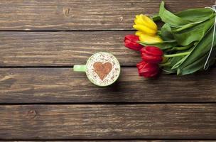 capuchino con forma de corazón y ramo de tulipanes foto