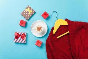 Geschenke und Kleiderbügel mit rotem Pullover
