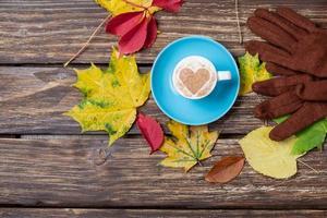 folhas de outono, luvas e xícara de café na mesa de madeira.