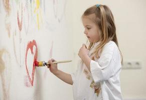 Cute girl painting a heart photo