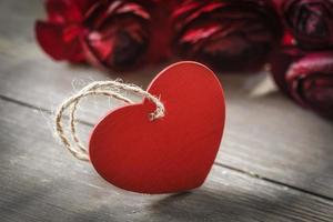 ranúnculos con corazón rojo sobre madera foto