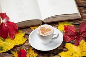 folhas de outono, livro e xícara de café na mesa de madeira.