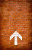 White arrow on brick wall