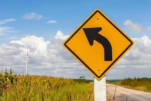 Left curved warning sign with windmill background in wind farm,
