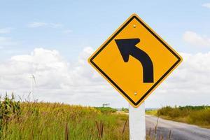 Señal de tráfico de carretera curva izquierda con fondo de molino de viento y claro foto