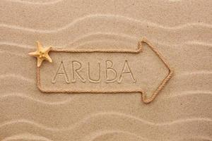 Arrow made of rope  the word Aruba on the sand