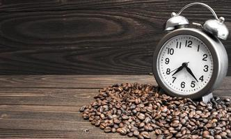 Despertador con campanas y granos de café derramados.