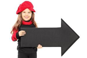 Cute little girl wearing red beret and holding black arrow