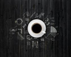 mesa cubierta con dibujos y una taza de café