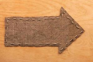 Arrow of burlap  lies on wooden  background