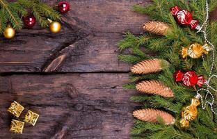 Cônes de sapin, sphères et guirlandes sur fond de bois