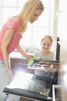 Happy mother and daughter removing cookie tray from oven