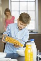 Boy pouring corn flakes in bowl
