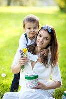 Beautiful kid and mom in spring park, flower and present