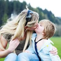 mother son outdoors kissing