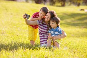 mãe feliz com dois filhos, tirando fotos no parque,