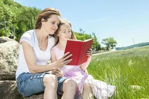 Little girl with mother reading a book photo