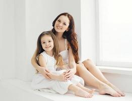 Portrait of beautiful mother and daughter at home in room photo