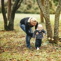 Happy young mom with lovely son in autumn park. photo