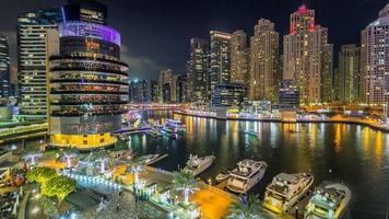 Vista de las torres de la marina de Dubai y el canal en el timelapse nocturno de Dubai