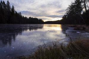 lago de agua dulce helada en la puesta de sol