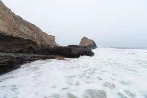 Rocas costeras y olas en la playa al amanecer.
