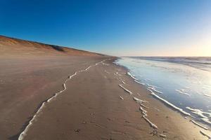playa de arena y olas del mar del norte foto