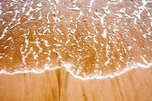 Sea wave over sand