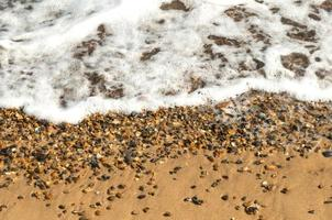 Ocean Wave Washes Over Sand and Pebble Beach photo