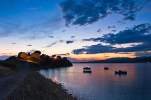 Sunset at Toroni bay, old roman fortress and fishing boats