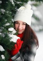 Beautiful woman outdoor behind snow covered pine tree