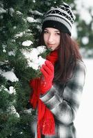 Young beautiful woman behind snow covered pine in winter