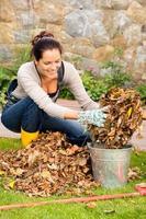 Mujer feliz poniendo hojas secas patio de la cuchara foto