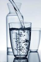 vaso lleno de agua y una jarra en el fondo foto
