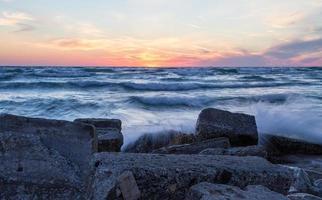 onde che si infrangono sulla costa al tramonto