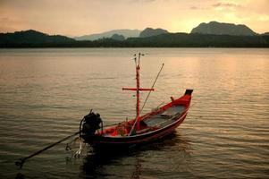 Sunset scenic view of traditional fishing long tailed boat.