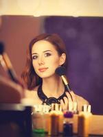 hermosa mujer pelirroja aplicando maquillaje cerca del espejo