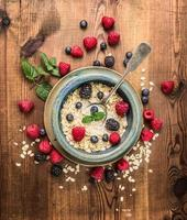 Porridge with milk , berries in rustik bowl on wooden background