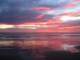naranja brillante y rosa atardecer en la playa del pacífico foto