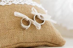 Wedding rings on hesium cushion with white ribbon photo