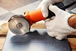 Cutting tiles with an electric grinder.