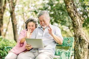 Happy senior Asian couple using laptop outside