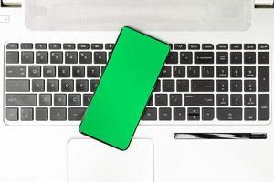 Smartphone de pantalla verde en el teclado del portátil