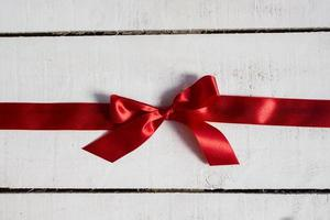 Red ribbon on white wooden background photo